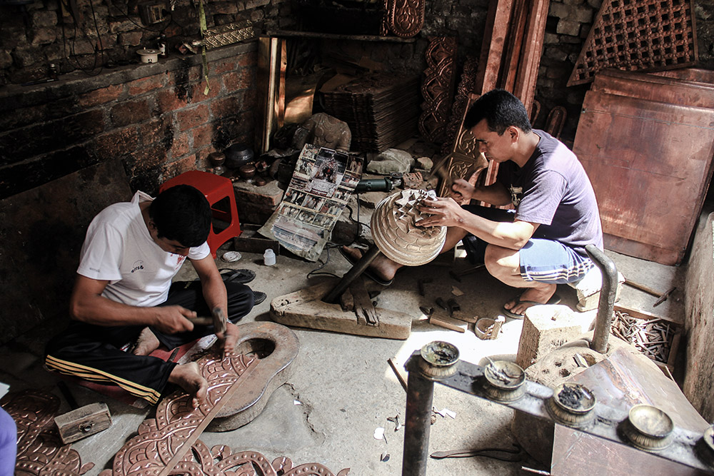 Tamrakar brothers decorating metal.